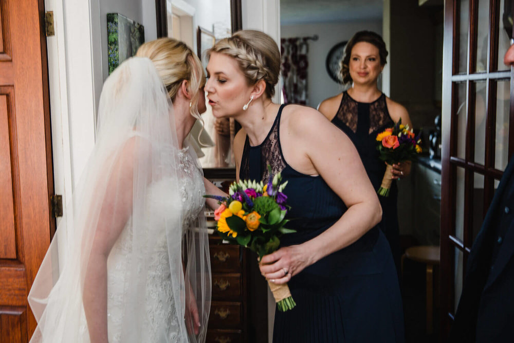 bridesmaid shares kiss with bride before leaving for ceremony