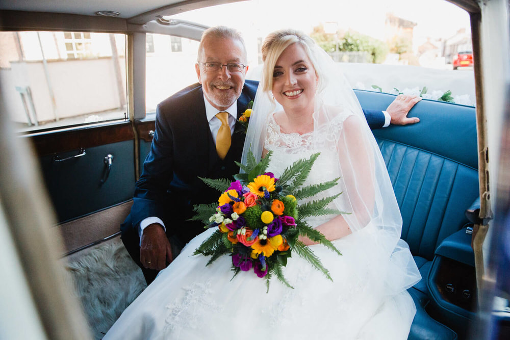 bride and father in wedding car before ceremony