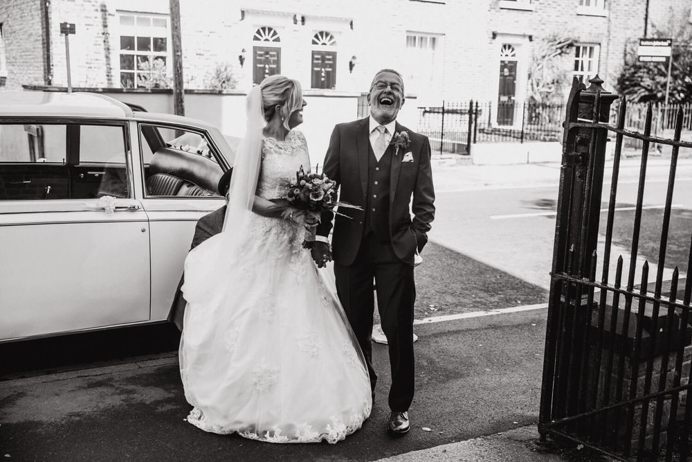 black and white photograph of bride and dad sharing joke outside church