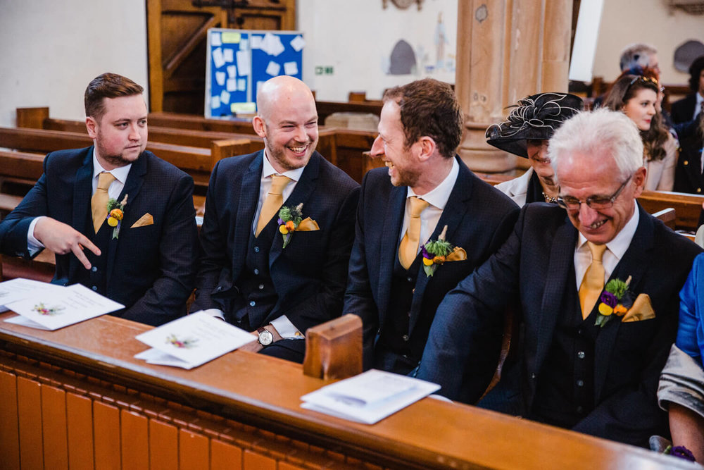 groomsmen at front pew of church laughing and joking