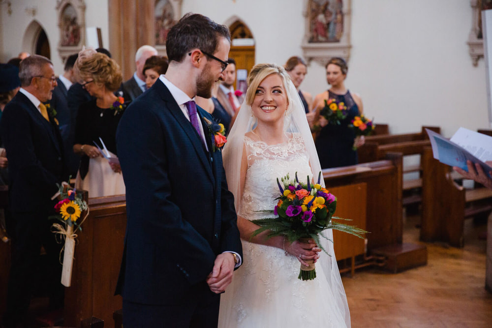 bride shares smile with groom at top of aisle