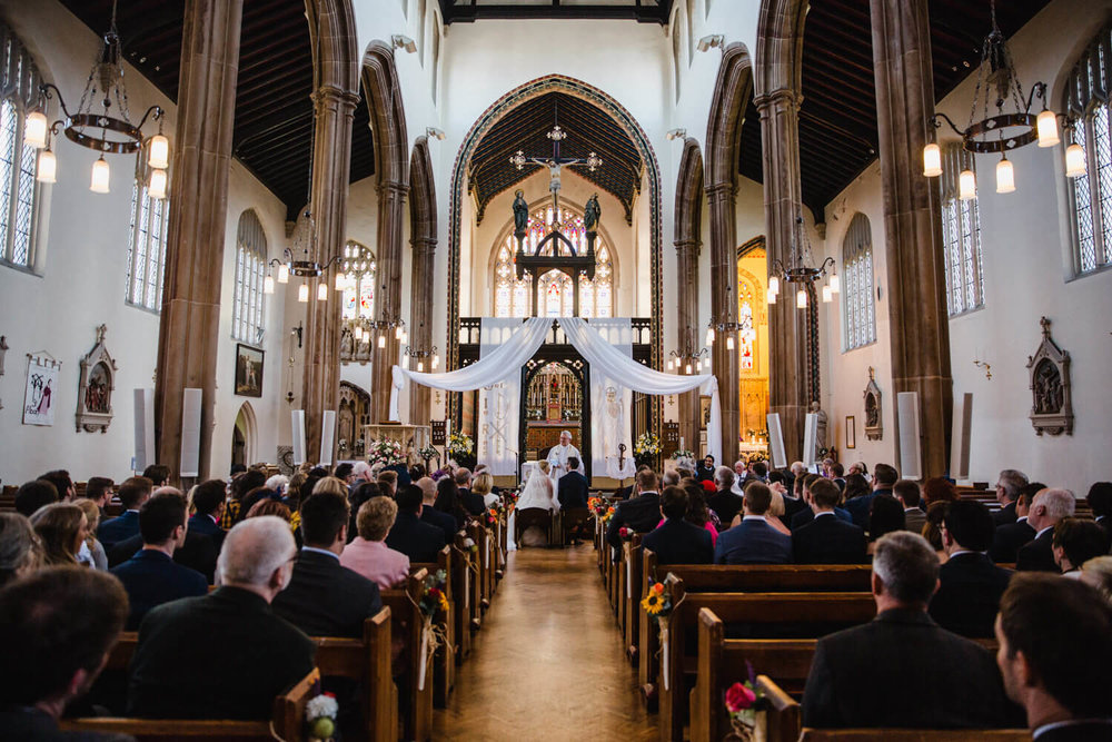 wide angle photograph from back of church covering the ceremony