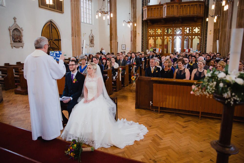 bride and groom sat with priest at top of ceremony