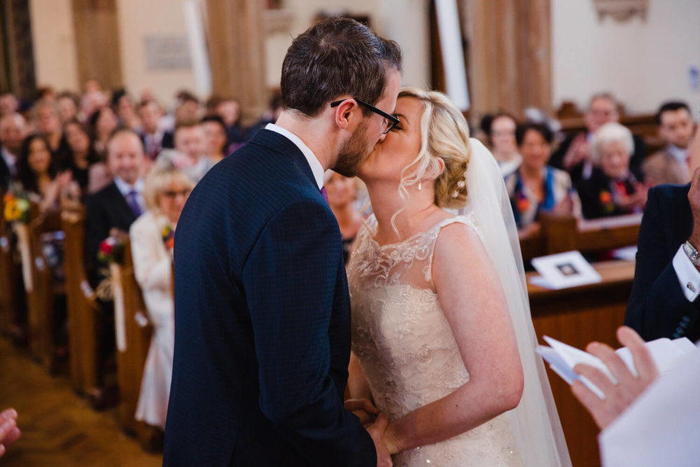 bride and groom first kiss in front of friends and family