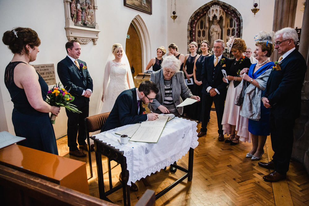groom signing the marriage certificate surrounded by family and bridesmaids