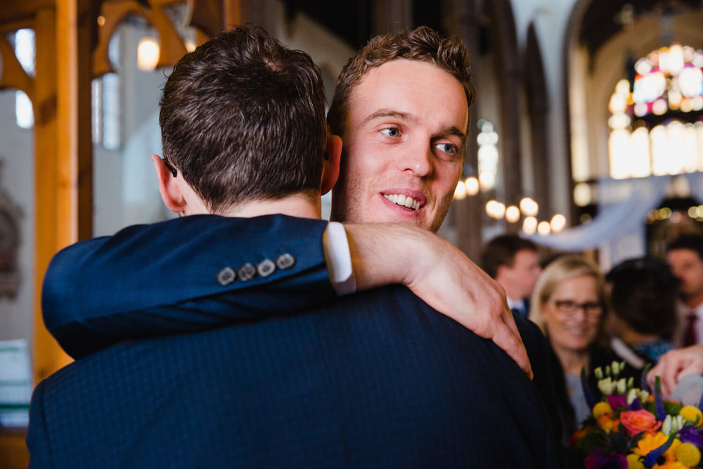 best man sharing hug with groom