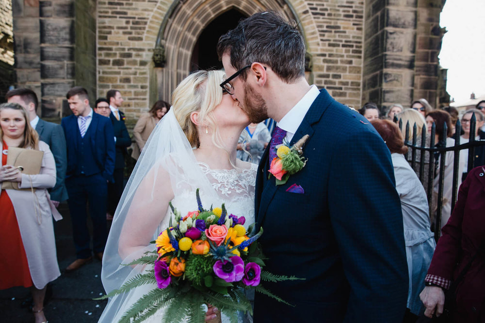 newlyweds share kiss after church service