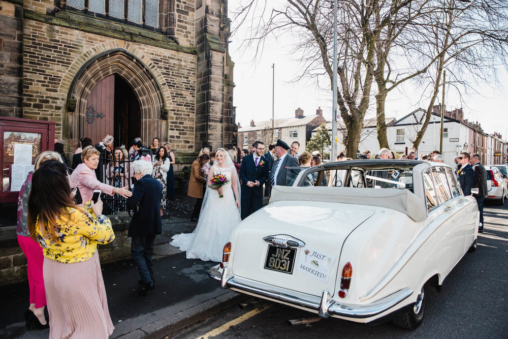 wide angle lens photograph of wedding car and guests outside church