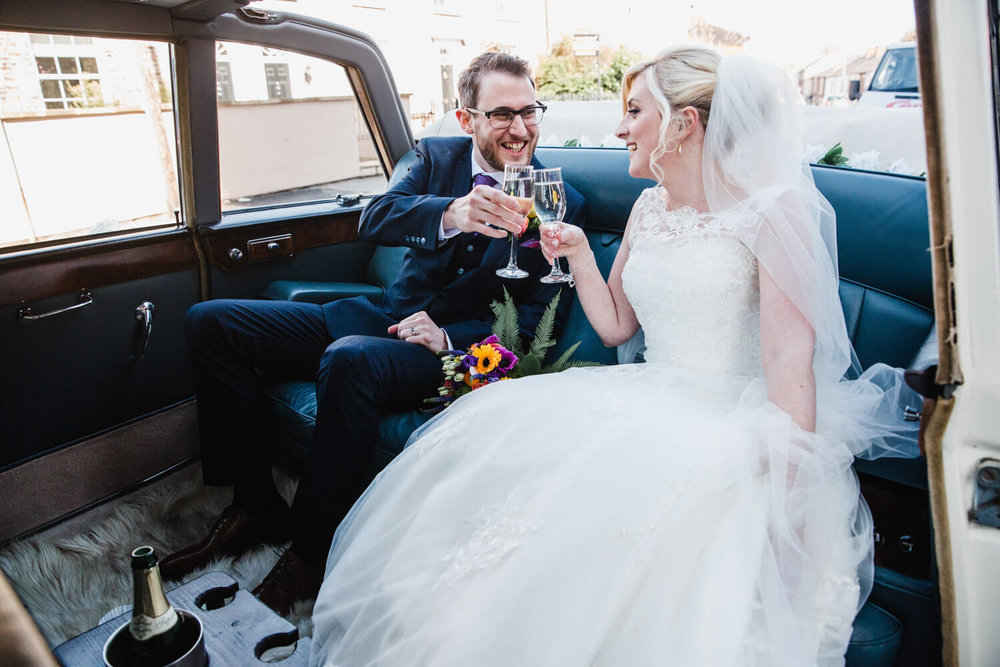 newly married couple sharing champagne in back of wedding car