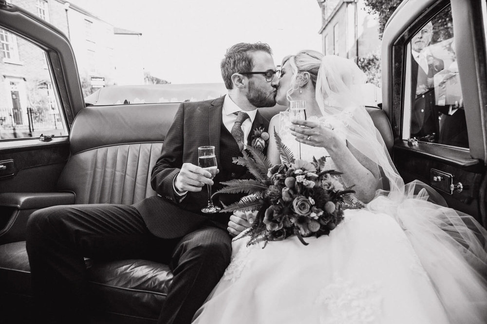 black and white photograph of newlyweds sharing kiss in back of car