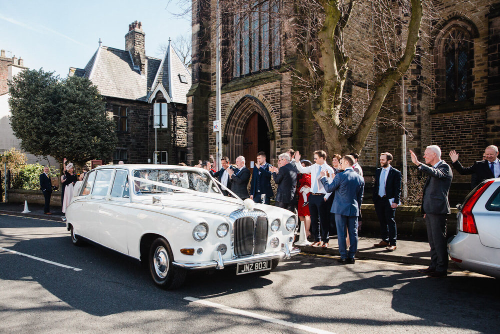 wedding guests waving off bride and groom as car travels to quarry bank mill