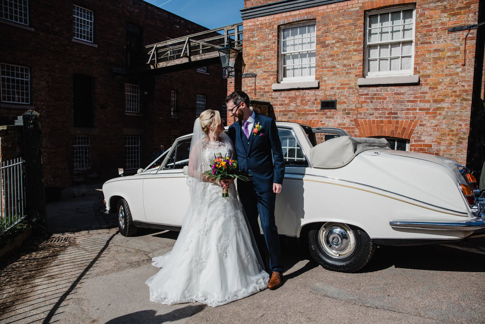 bride and groom arrive at quarry bank mill with wedding car