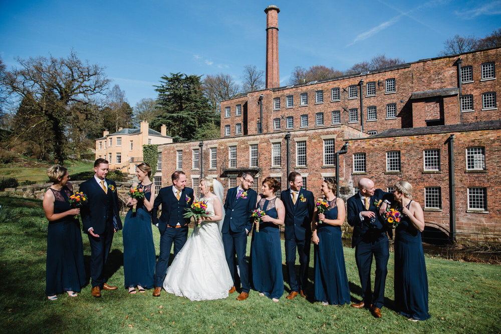 bridal party group shot in front of quarry bank mill
