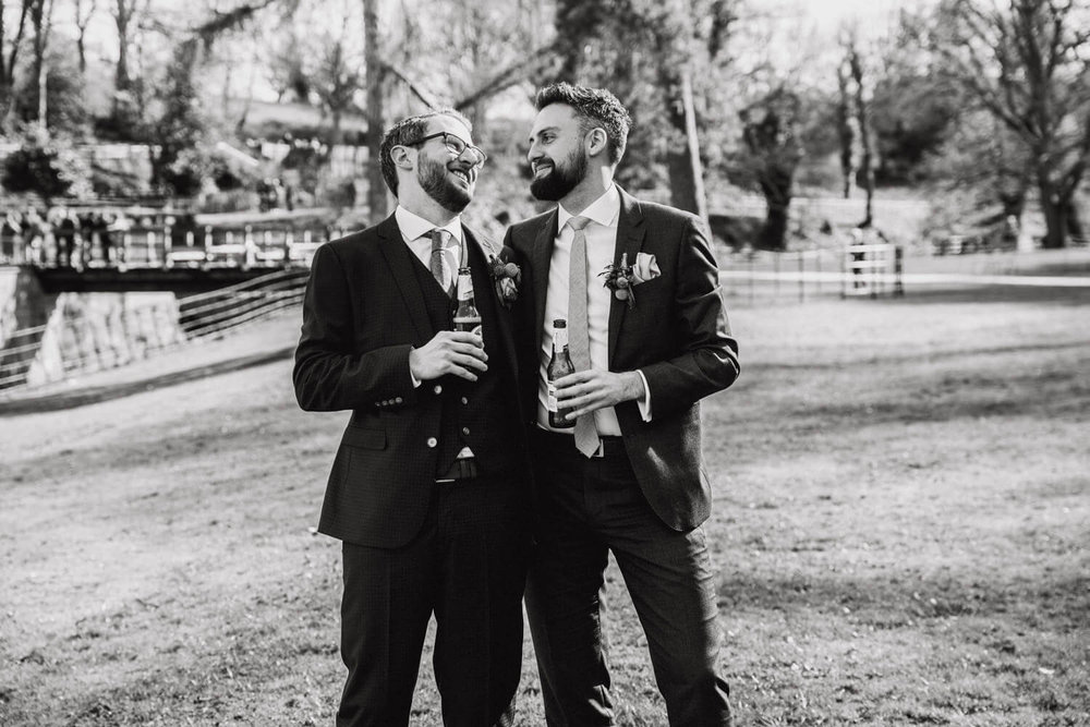 groom and best man having beers on lawn of quarry bank mill