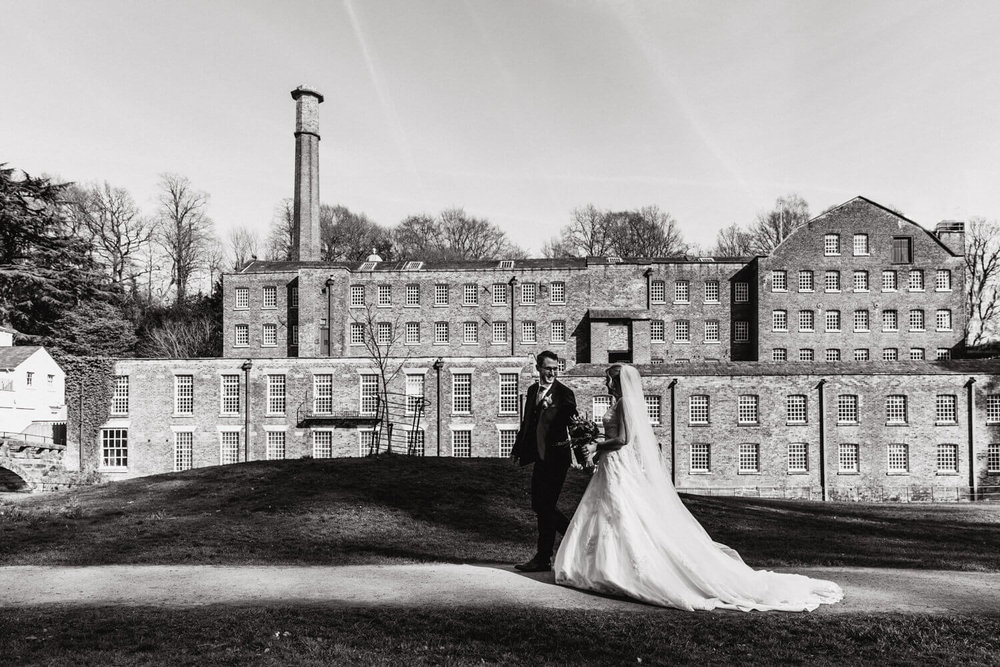 bride and groom take a stroll in the grounds of quarry bank mill