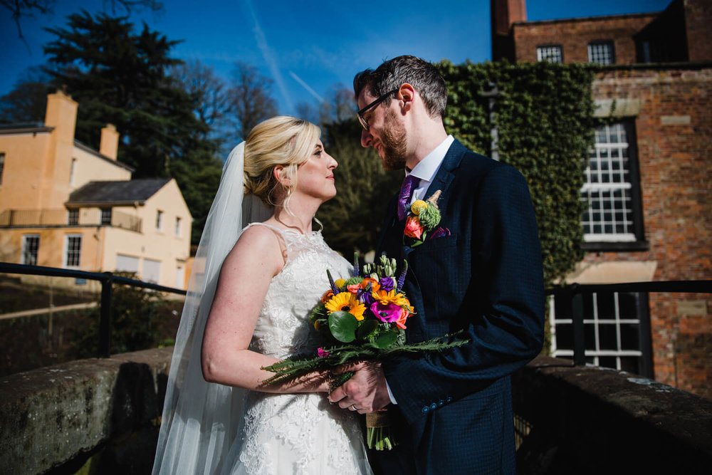 bride and groom holding bouquet of flowers on bridge at quarry bank mill