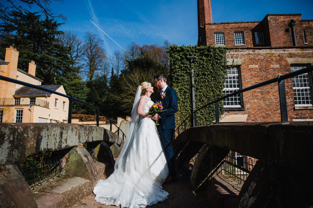 wider angle photograph of married couple on bridge
