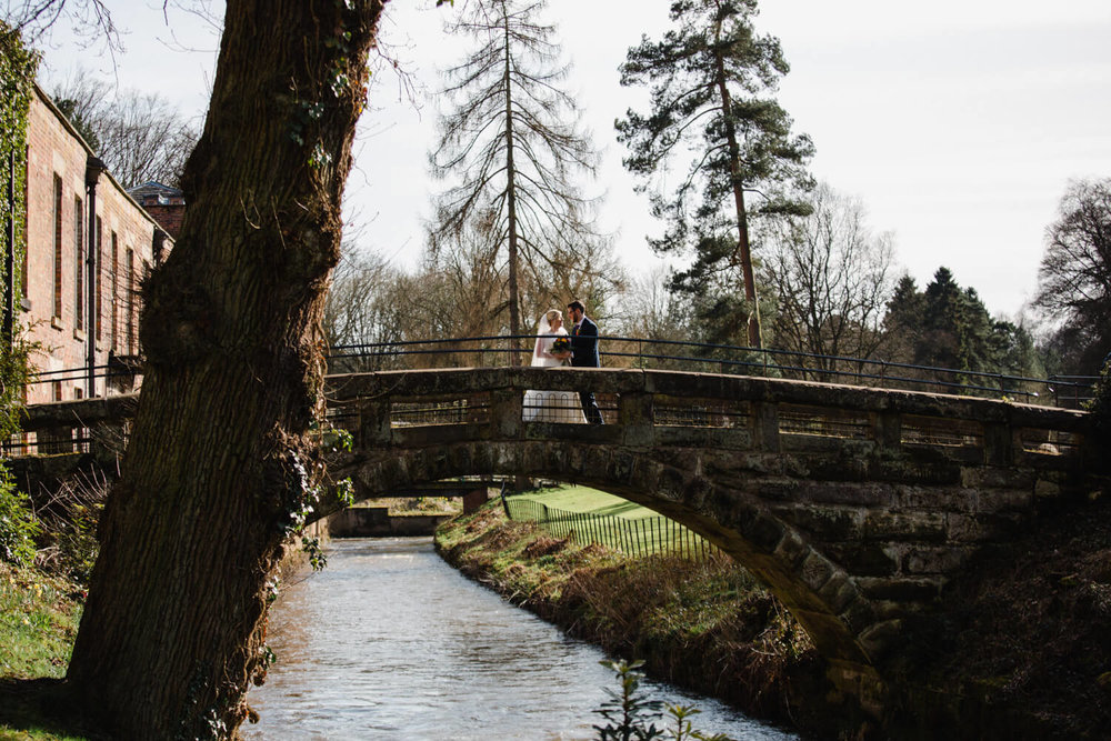 newlyweds on bridge for wedding portrait at quarry bank mill