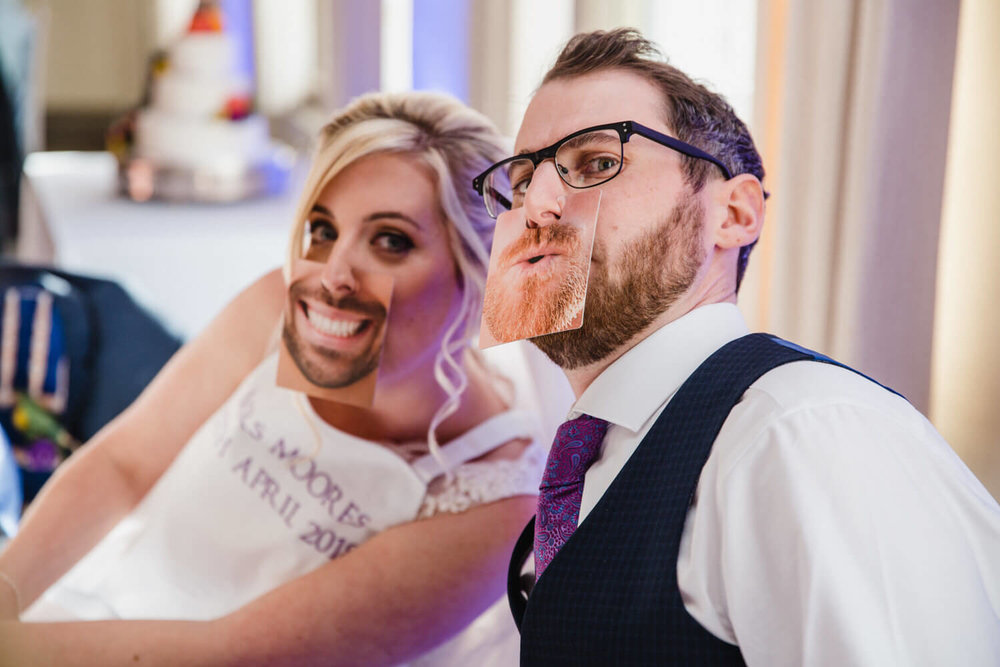bride and groom wearing mouth beer mats under noses