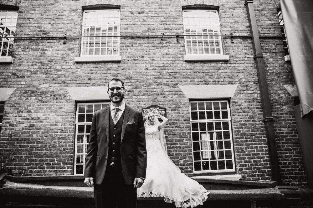 bride and groom portraits in industrial courtyard of mill
