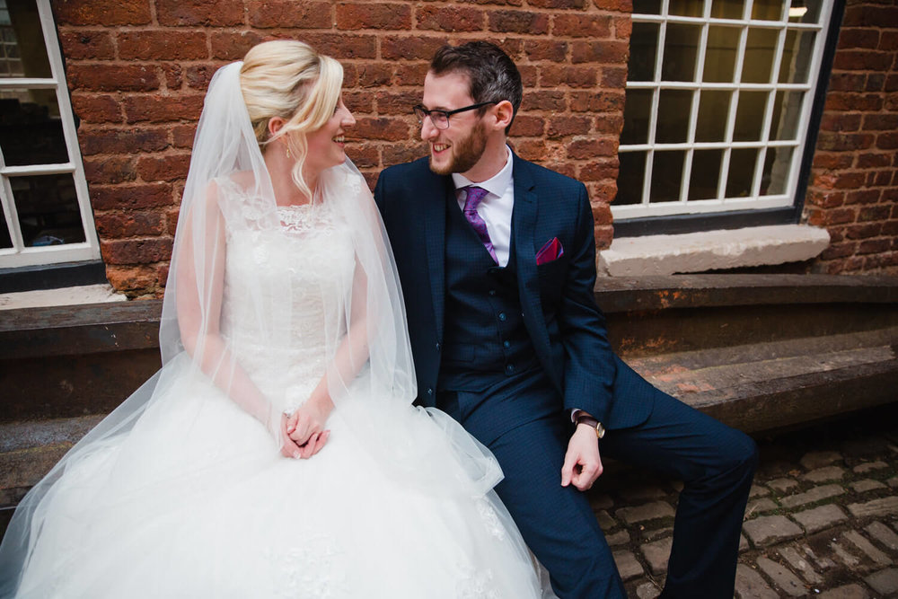 newlyweds sharing a joke in courtyard of quarry bank mill
