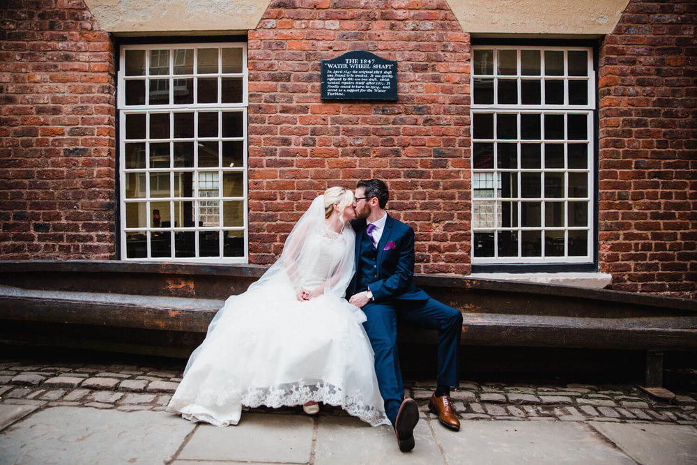 newlyweds share kiss on waterwheel shaft in courtyard at quarry bank mill