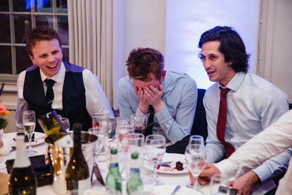 wedding guests laughing with head in hands