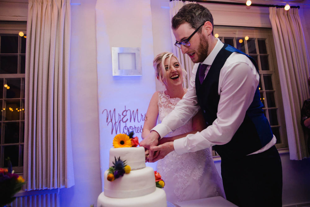 bride and groom cut into wedding cake at quarry bank mill