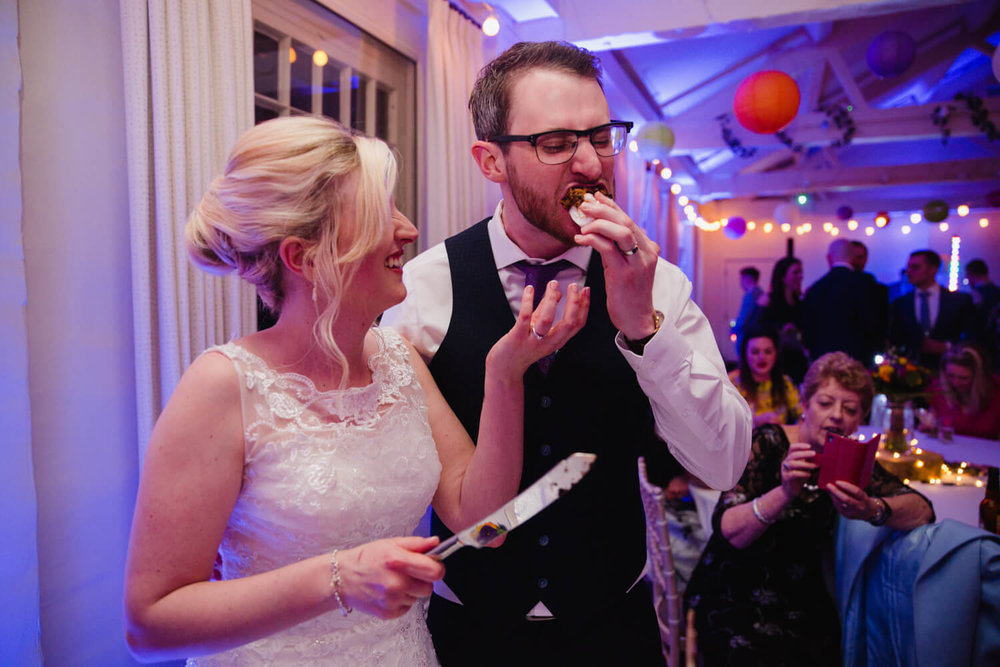 groom takes a bite out of wedding cake