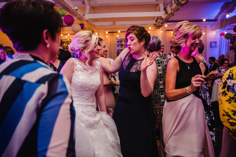 bride dances with bridesmaid sister