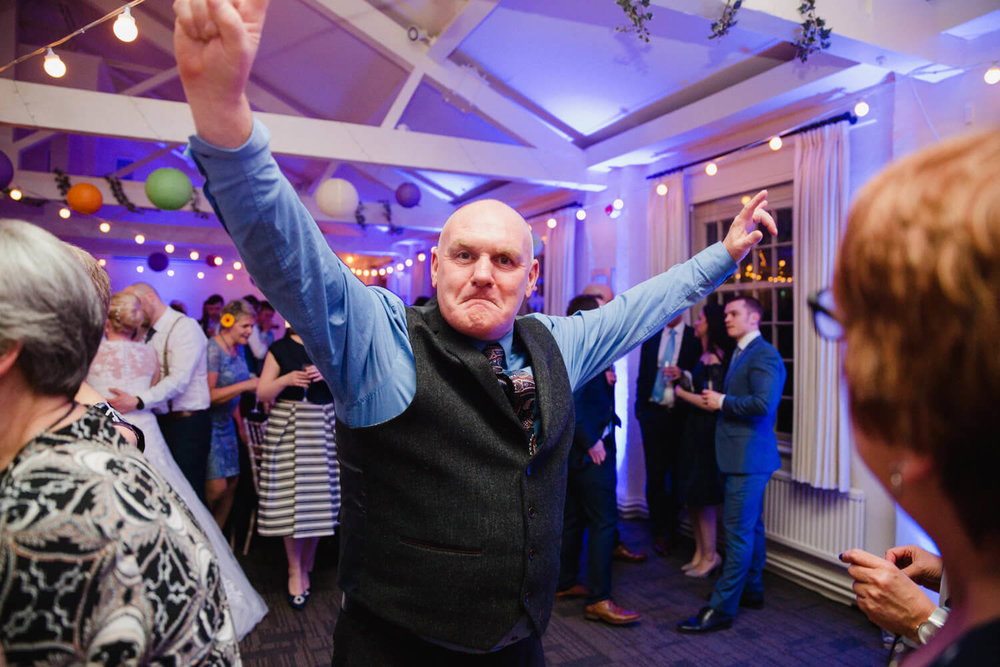 wedding guest poses with arms in air