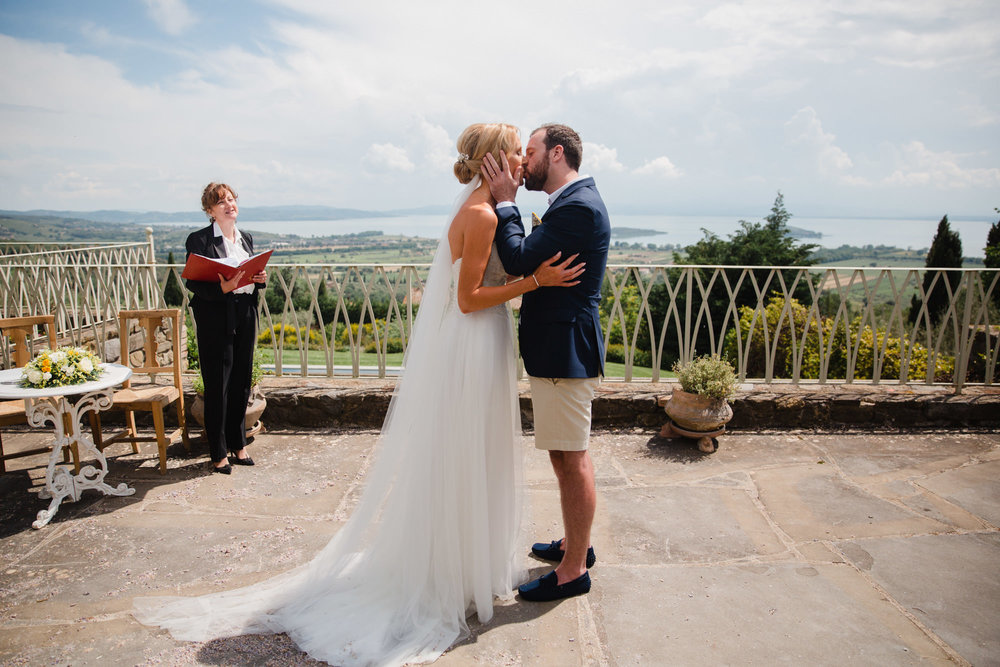 Nic and Phil's first kiss on the terrace of their Lake Trasimeno villa, watched on by Diane Rossi 'Blessings from Italy' Italian wedding celebrant.