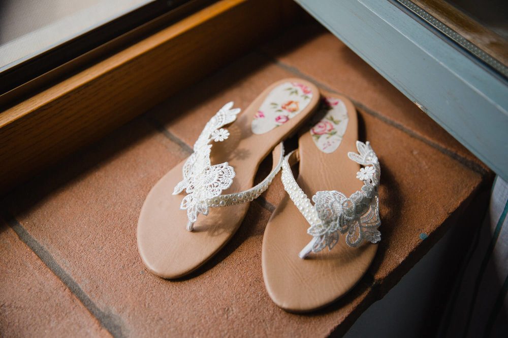 floral wedding sandals on window ledge