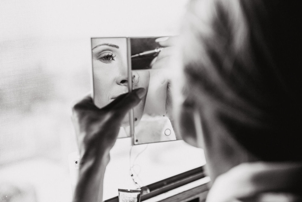 black and white photograph of bride preparing make up in mirror