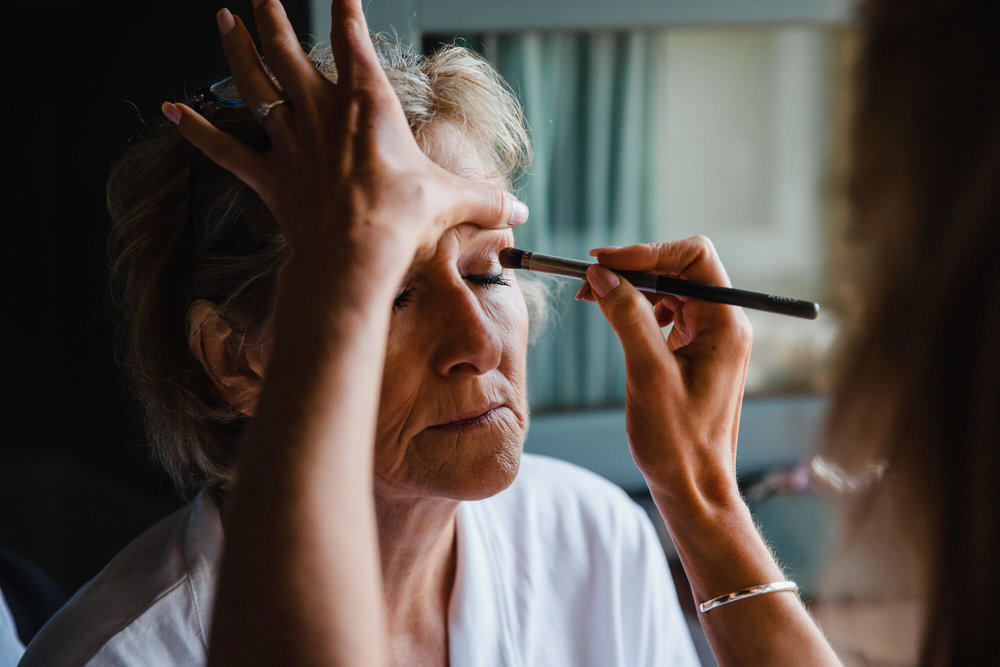 close up of mother of bride having mascara put on eye lashes