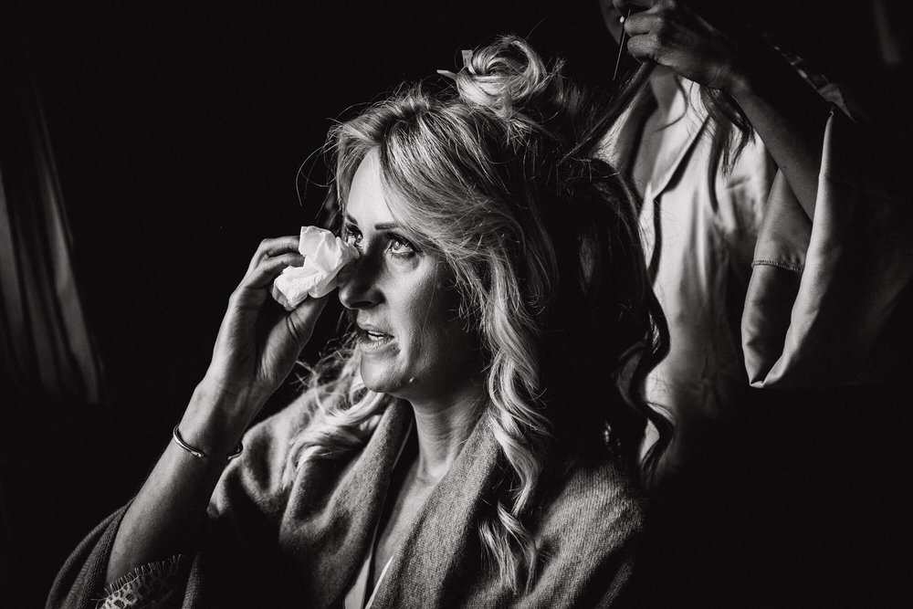 emotional black and white photograph of bride wiping away a tear during preparation