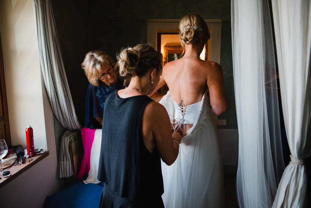 sister of bride helps fasten dress