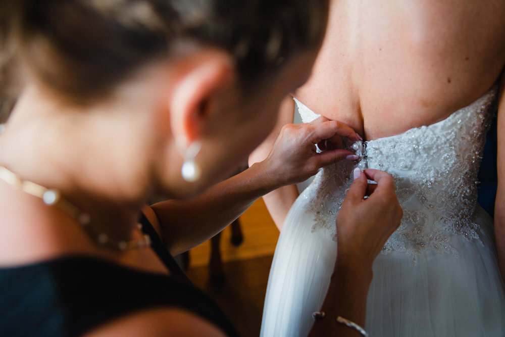 close up of wedding dress buttons being fastened