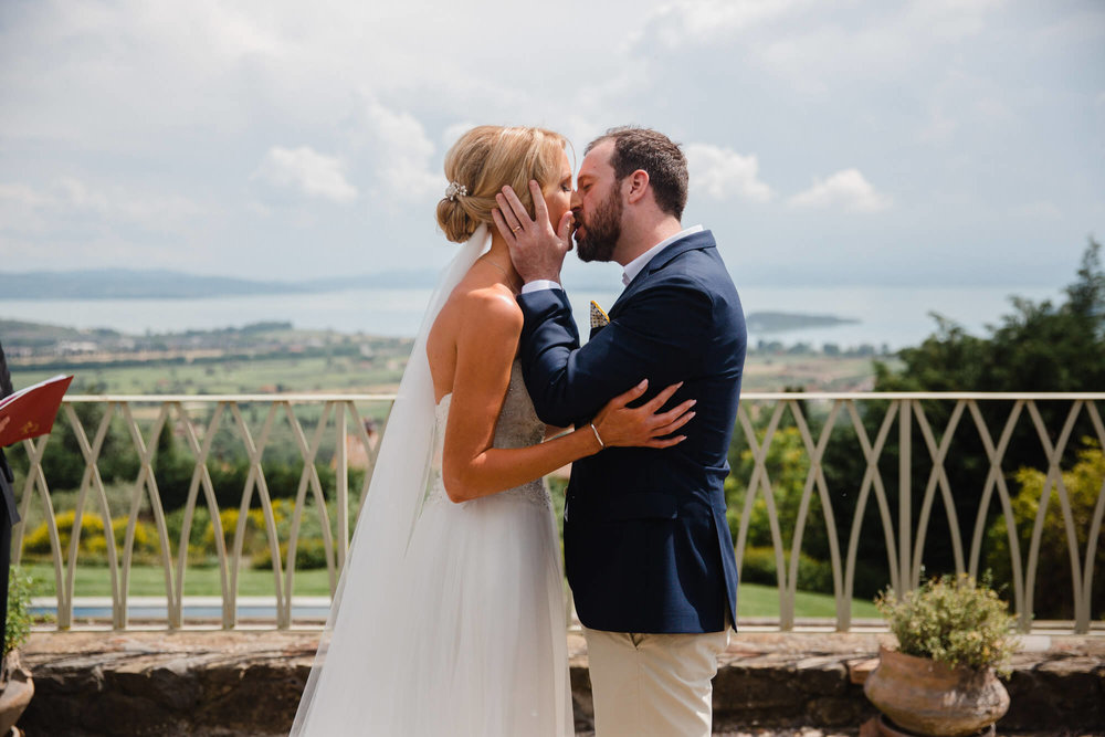 first kiss of bride and groom on terrace of tuscany villa