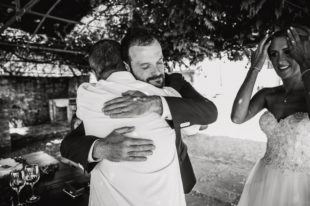 black and white intimate photograph of groom hugging dad after ceremony