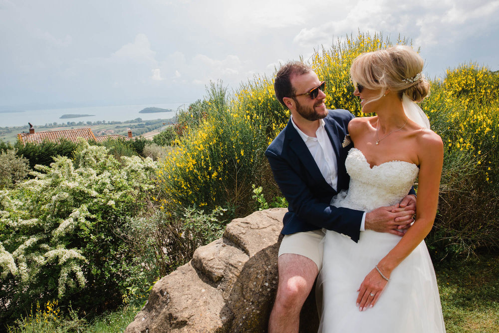 bride and groom share hug with rolling tuscany backdrop behind