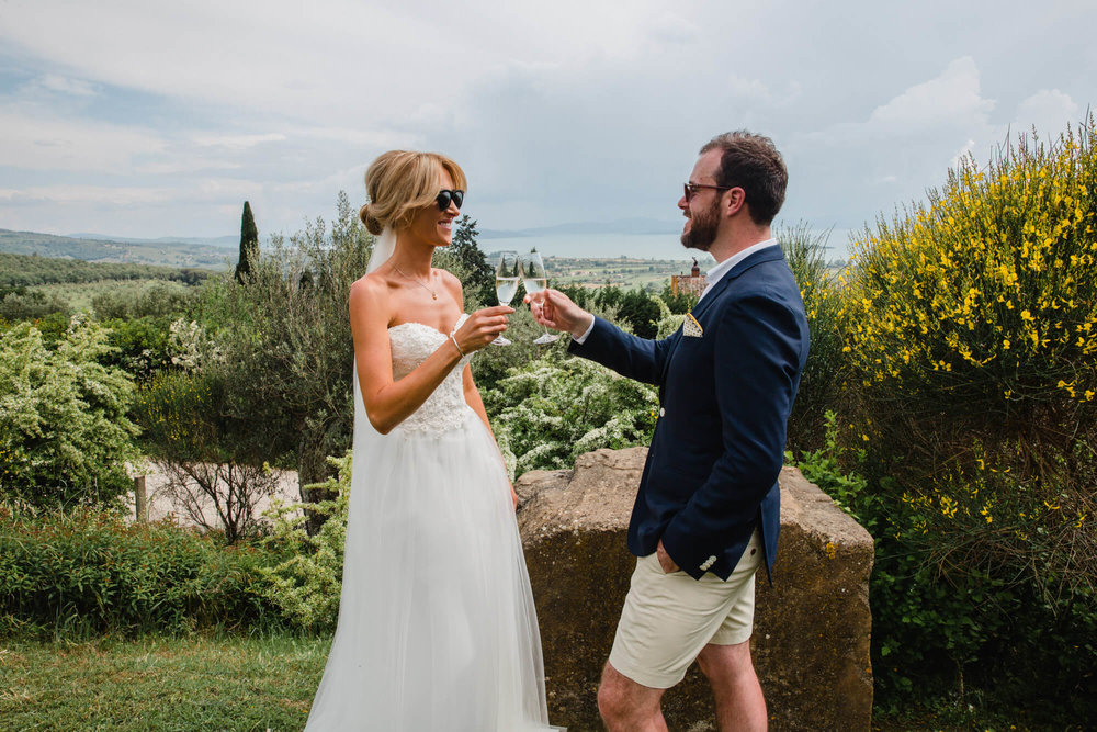 newlyweds cheers with champagne glasses in tuscany garden