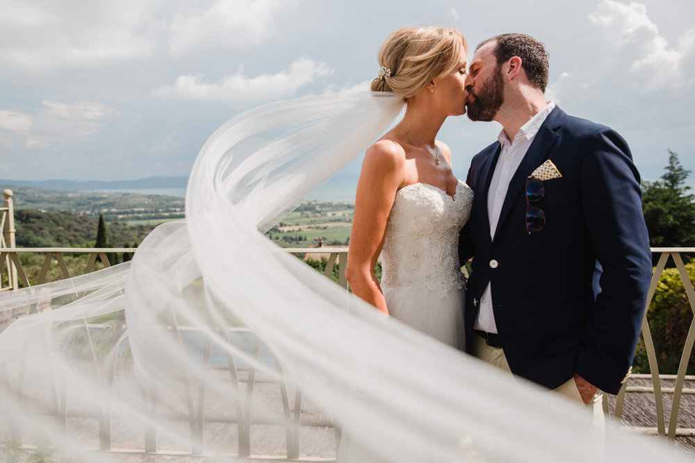 newlyweds kissing on tuscany balcony with veil blowing in the wind