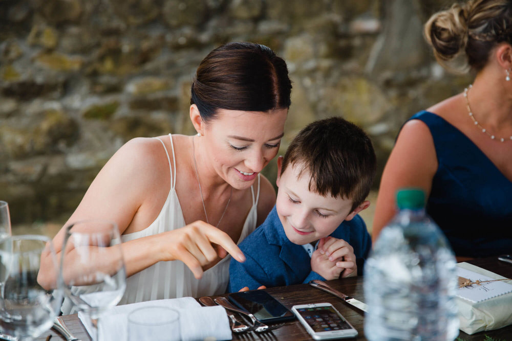 wedding guest playing on mobile phone with page boy at table