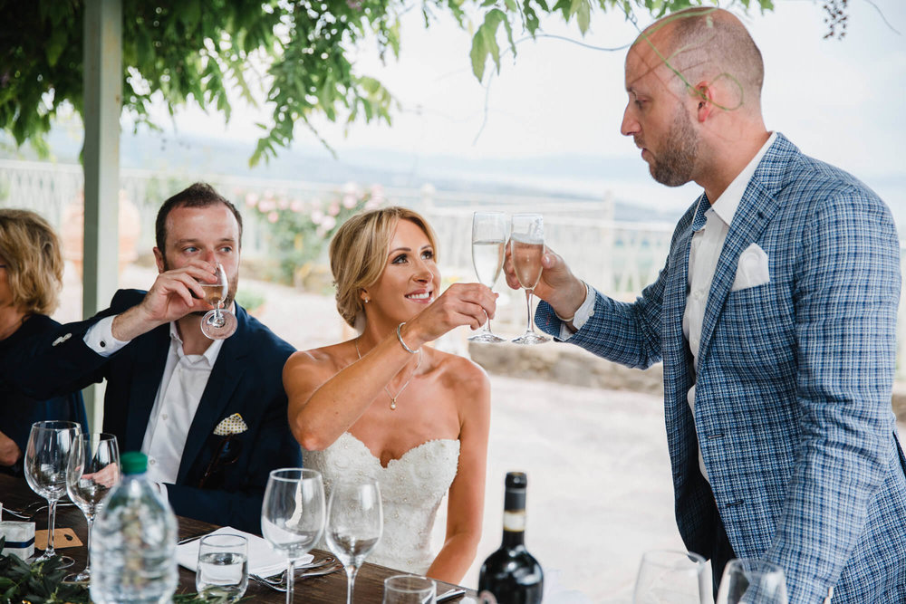 bride clinking glasses with groomsman at the end of wedding speeches