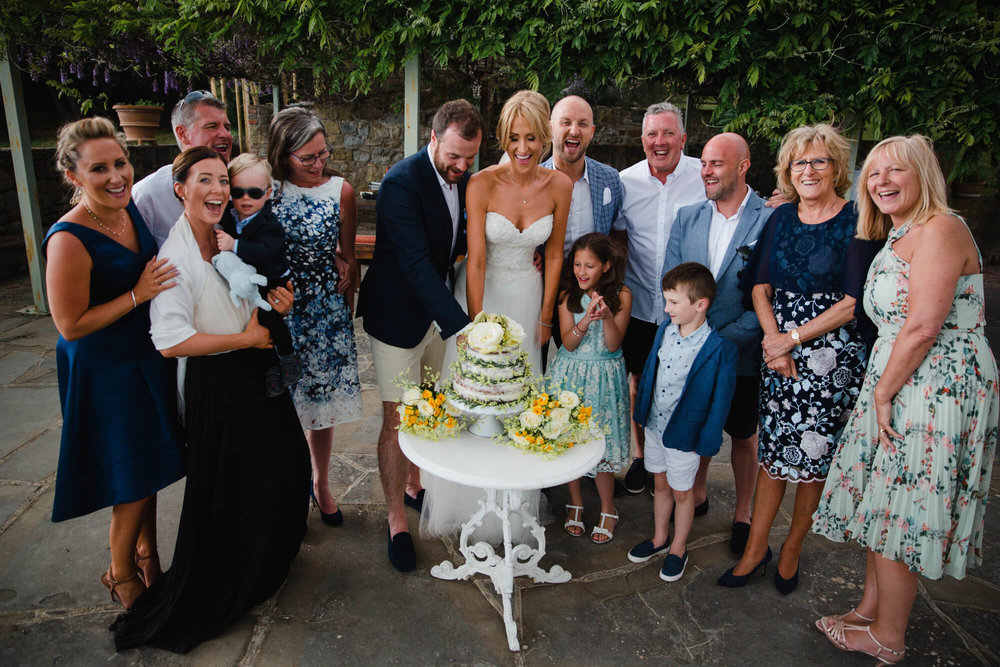 family gather on balcony for the cutting of the wedding cake