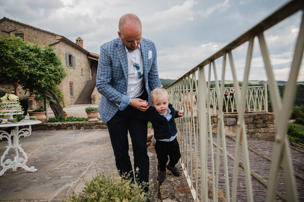 baby learning to walk along balcony of tuscany wedding