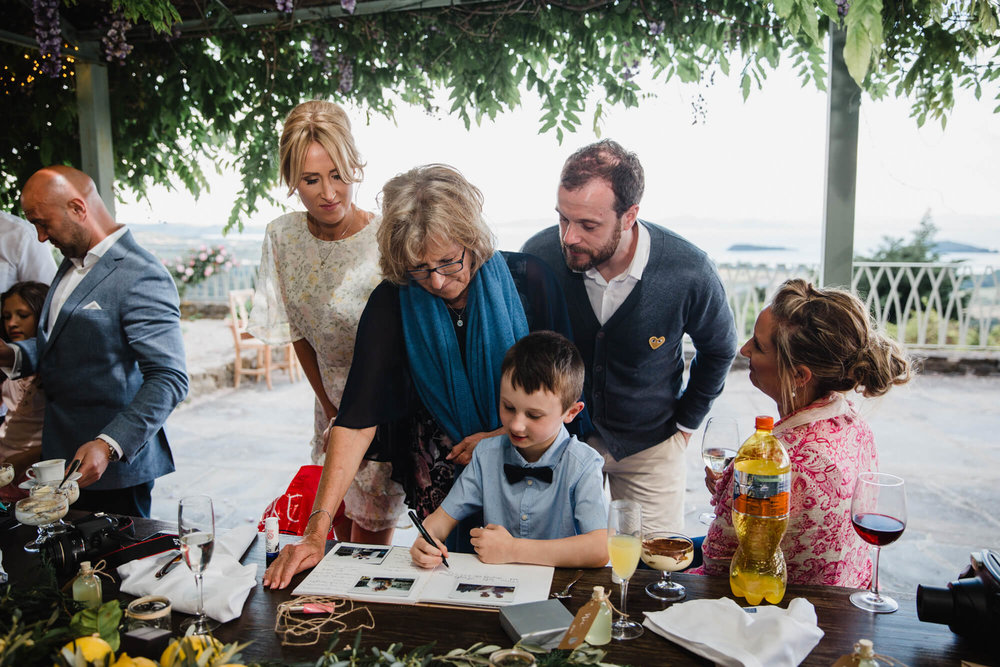 family and groom look on at page boy writing in the wedding guest book