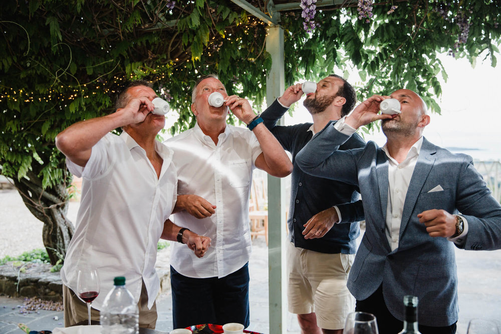 groom and groomsmen taking a shot of strong Italian espresso