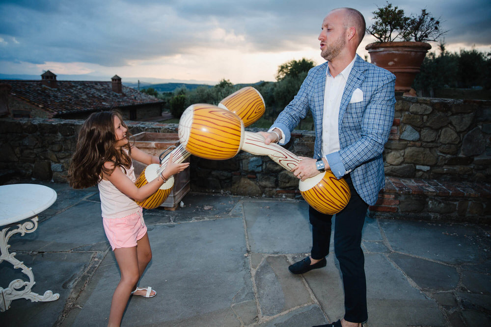 bridesmaid fights with groomsman on terrace with inflatable pogo sticks